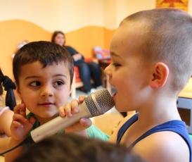 Kita-Kinder sprechen in ein Mikrofon